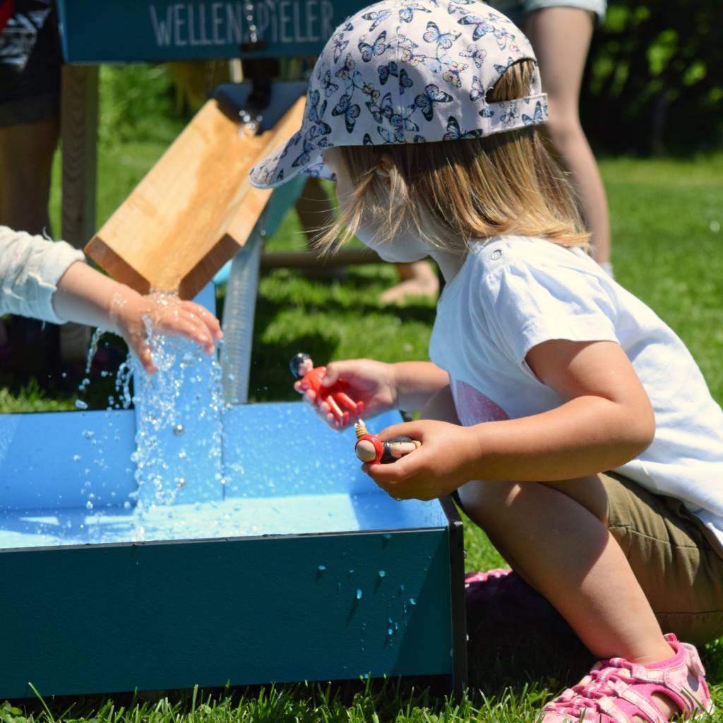 Kleines Mädchen spielt am WELLENSPIELER Wasserspiel Bodenbecken