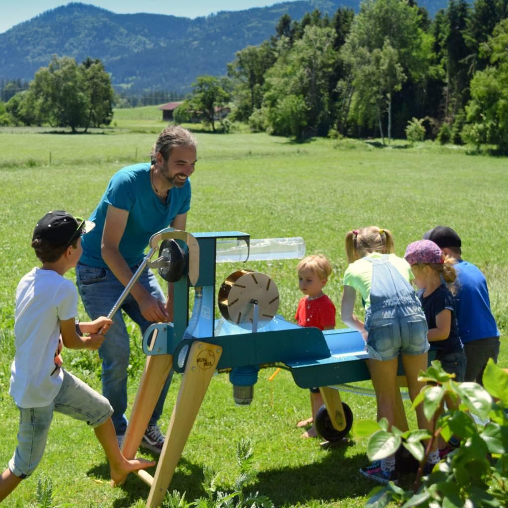 Der Erfinder Robert Jahnsmüller spielt mit Kindern am WELLENSPIELER Wasserspiel